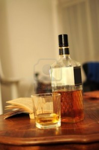 glass-of-whiskey-bottle-and-opened-book-on-home-table